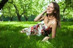 De mooie vrouw ligt op het gras Royalty-vrije Stock Fotografie