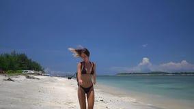 De mooie vrouw loopt en loopt op wit zandig strand van de kristaloceaan stock video