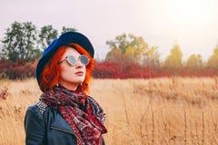 De mooie vrouw loopt in de herfst in het park in het weer stock afbeeldingen