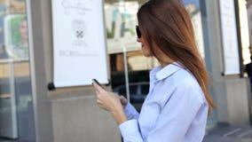 De mooie vrouw maakt beelden door haar mobiele telefoon in een straat voor stadswandelgalerij stock footage