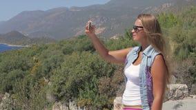 De mooie vrouw maakt een foto van landschap gebruikend de telefooncamera van de smartphone mobiele cel stock video