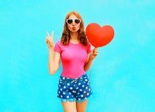 De mooie vrouw maakt een luchtkus houdt een rode ballon in de vorm Royalty-vrije Stock Foto