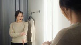 De mooie vrouw meet de kleren in een montageruimte stock videobeelden