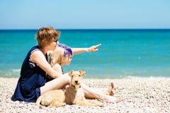 De mooie vrouw met aanbiddelijke dochter en de hond zitten op het strand Stock Afbeelding