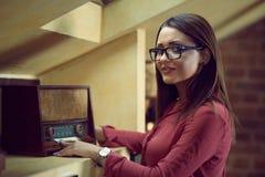 De mooie vrouw met bril luistert aan een oude radio Royalty-vrije Stock Afbeelding
