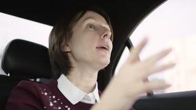 De mooie vrouw met bruin haar in witte blouse en het kastanjebruine sweater berijden in auto en verklaren de juiste manier aan ha stock footage