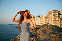 De mooie vrouw met de kleding van het de zomerstrand op tribunes op een rotsstrand en geniet van zon op vakantie Aantrekkelijk mo Royalty-vrije Stock Afbeeldingen