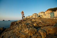 De mooie vrouw met de kleding van het de zomerstrand op tribunes op een rotsstrand en geniet van zon op vakantie Aantrekkelijk mo Royalty-vrije Stock Fotografie