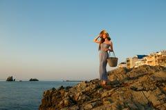 De mooie vrouw met de kleding van het de zomerstrand op tribunes op een rotsstrand en geniet van zon op vakantie Aantrekkelijk mo Royalty-vrije Stock Afbeelding