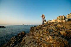 De mooie vrouw met de kleding van het de zomerstrand op tribunes op een rotsstrand en geniet van zon op vakantie Aantrekkelijk mo Stock Foto