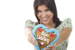 De mooie vrouw met dirndl en gingerbred hart Royalty-vrije Stock Foto