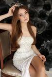 De mooie vrouw met donker haar draagt elegante kleding en kostbare kroon Royalty-vrije Stock Foto