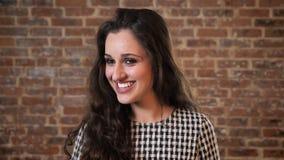 De mooie vrouw met donker krullend haar glimlacht, het springen, baksteenachtergrond stock video