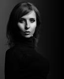 De mooie vrouw met elegante hals in manier zwarte kleding kijkt stock fotografie