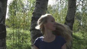 De mooie vrouw met glimlach kijkt uit van berk en golvenhaar Langzame Motie stock video