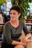 De mooie vrouw met kort kapsel zit op een de zomerterras bij a Stock Afbeelding