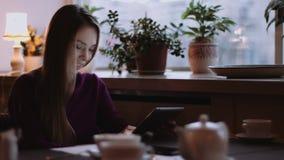 De mooie vrouw met lang haar gebruikt gadget stock videobeelden