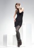 De mooie vrouw met lange sexy benen kleedde het elegante stellen in de studio Royalty-vrije Stock Afbeeldingen