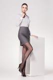 De mooie vrouw met lange sexy benen kleedde het elegante stellen in de studio royalty-vrije stock foto's