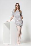 De mooie vrouw met lange sexy benen kleedde het elegante stellen in de studio Royalty-vrije Stock Afbeelding