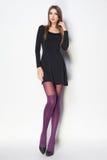 De mooie vrouw met lange sexy benen kleedde het elegante stellen in Th royalty-vrije stock fotografie