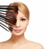 De mooie vrouw met make-up borstelt dichtbij aantrekkelijk gezicht Royalty-vrije Stock Foto's