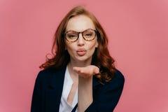 De mooie vrouw met rood haar houdt lippen gevouwen, verzendt luchtkus, uitdrukt de liefde aan vriend optische binnen geklede glaz royalty-vrije stock foto's