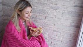 De mooie vrouw met roze plaid houdt een plak van pizza in haar hand en eet het stock fotografie