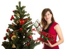 De mooie vrouw met stelt dichtbij Kerstboom voor Stock Foto's