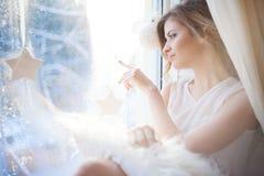 de mooie vrouw met verse dagelijkse make-up en romantisch golvend kapsel, die bij de vensterbank zitten, trekt op glas royalty-vrije stock afbeelding