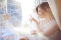 de mooie vrouw met verse dagelijkse make-up en romantisch golvend kapsel, die bij de vensterbank zitten, trekt op glas royalty-vrije stock foto's