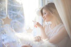de mooie vrouw met verse dagelijkse make-up en romantisch golvend kapsel, die bij de vensterbank zitten, trekt op glas stock foto's
