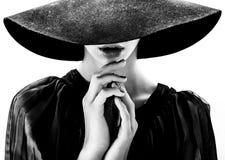 De mooie vrouw met volledige lippen in zwarte hoed stelt Royalty-vrije Stock Afbeeldingen