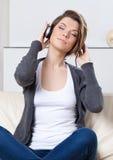 De mooie vrouw in oortelefoons luistert aan muziek Royalty-vrije Stock Afbeeldingen
