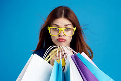 De mooie vrouw op blauwe achtergrond in gele glazen houdt pakketten, het winkelen, portret Stock Foto