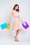 De mooie vrouw op een lichte achtergrond houdt pakketten, het winkelen, het winkelen Royalty-vrije Stock Fotografie