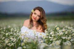 De mooie vrouw op het kamillegebied draagt witte kleding, de lentetijd Royalty-vrije Stock Foto's