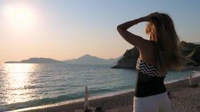De mooie Vrouw is op het Strand Genietend van Lettend op de Zonsondergang rechtmaakt Haar 4k stock footage