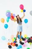 De mooie vrouw op hoge hielen kijkt het gelukkige spelen met ballons Stock Fotografie