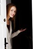 De mooie vrouw opent deur en nodigt om binnen te komen uit. Royalty-vrije Stock Fotografie