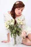De mooie vrouw in openwork kleding zit op vloer dichtbij vaas Stock Foto