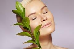 De mooie vrouw past Organisch Schoonheidsmiddel toe Kuuroord en wellness Model met schone huid Gezondheidszorg Beeld met blad stock afbeelding