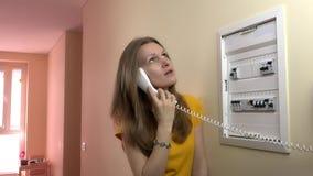 De mooie vrouw raadpleegt elektricien op draadtelefoon dichtbij stroomonderbrekerdoos stock videobeelden