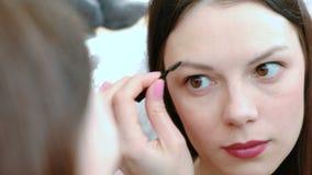 De mooie vrouw schildert haar wenkbrauwen Close-upgezicht voor de spiegel stock video