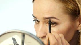 De mooie vrouw schildert haar wenkbrauwen en het doen van dagelijkse make-up met make-upborstel voor kleine spiegel 4K stock footage