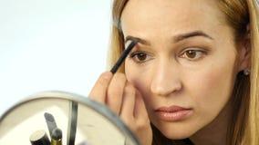 De mooie vrouw schildert haar wenkbrauwen en het doen van dagelijkse make-up met make-upborstel voor kleine spiegel Langzame Moti stock videobeelden
