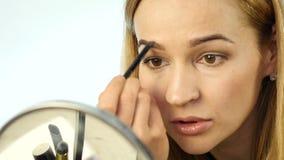 De mooie vrouw schildert haar wenkbrauwen en het doen van dagelijkse make-up met make-upborstel voor kleine spiegel Langzame Moti stock video