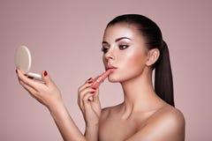 De mooie vrouw schildert lippen met lippenstift Royalty-vrije Stock Fotografie
