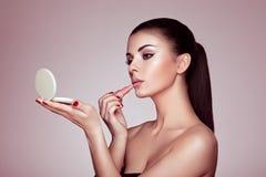 De mooie vrouw schildert lippen met lippenstift Royalty-vrije Stock Foto's