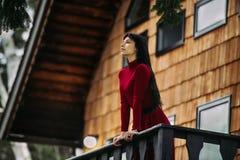De mooie vrouw status op de portiek van blokhuis bij bos en geniet van de mening stock foto